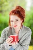Красивая молодая женщина при красные волосы сидя в саде, ослабляющ, выпивая кофе стоковые изображения rf