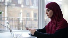 Красивая молодая женщина при фиолетовое hijab покрывая ее голову перечисляет ее smartphone, сидя около компьтер-книжки в свете акции видеоматериалы