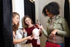 Красивая молодая женщина прося мнение друзей в примерочной магазина женское бельё Женщина пробует дальше бюстгальтер внутри Стоковые Изображения