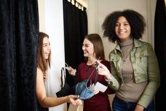 Красивая молодая женщина прося мнение друзей в примерочной магазина женское бельё Женщина пробует дальше бюстгальтер внутри Стоковая Фотография RF