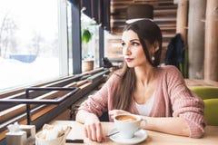 Красивая молодая женщина сидит на таблице в кафе с чашкой кофе и смотрит вне окно стоковое изображение rf