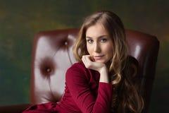 Красивая молодая женщина сидя в кресле крыто Смотреть в c стоковые фото