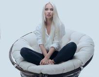 Красивая молодая женщина сидя на кресле в большом удобном кресле стоковые фотографии rf