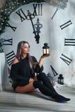 Красивая молодая женщина сидя на предпосылке большого оформления рождества часов, держащ электрофонарь, ждать праздник стоковая фотография rf