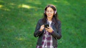 Красивая молодая женщина смешанной гонки слушая музыку на наушниках со смартфоном Испанские танцы девушки хипстера к видеоматериал