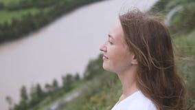 Красивая молодая женщина смотря вверх на небе вне к взгляду горизонта поверх горы сток-видео