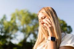 Красивая молодая женщина со светлыми волосами используя мобильный телефон на открытом воздухе Стильная девушка делая selfie стоковое фото