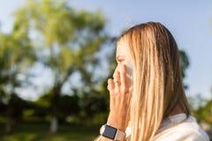Красивая молодая женщина со светлыми волосами используя мобильный телефон на открытом воздухе Стильная девушка делая selfie стоковые изображения rf