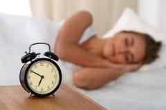 Красивая молодая женщина спать и усмехаясь пока лежащ в кровати удобно и блаженно на предпосылке сигнала тревоги стоковое изображение