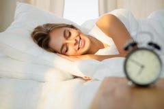 Красивая молодая женщина спать пока лежащ в кровати удобно и блаженно солнечный луч рассветает на ее стороне стоковое фото