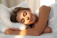 Красивая молодая женщина спать пока лежащ в кровати удобно и блаженно Рассвет солнечного луча на ее стороне стоковое фото