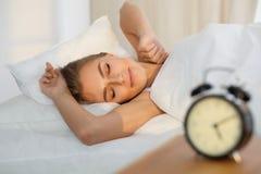 Красивая молодая женщина спать пока лежащ в кровати удобно и блаженно солнечный луч рассветает на ее стороне стоковое изображение