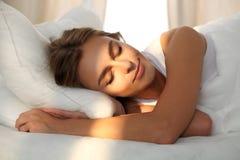 Красивая молодая женщина спать пока лежащ в кровати удобно и блаженно Рассвет солнечного луча на ее стороне стоковое изображение