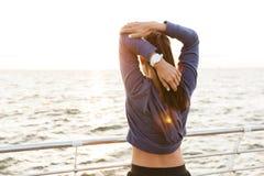 Красивая молодая женщина спорт outdoors на музыке пляжа слушая с наушниками делает протягивать тренировки стоковые изображения rf