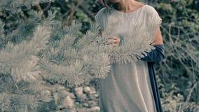 Красивая молодая женщина стоит в coniferous лесе и поет песню сток-видео