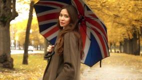 Красивая молодая женщина стоя с зонтиком на переулке осени на дождливый день Стоковая Фотография