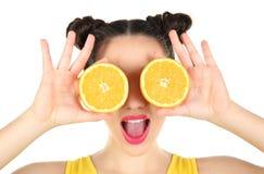 Красивая молодая женщина с апельсином уменьшать около глаз Стоковые Изображения RF