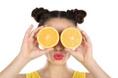 Красивая молодая женщина с апельсином уменьшать около глаз Стоковое Изображение