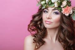 Красивая молодая женщина с венком вьющиеся волосы и цветка на ее голове на розовой девушке красоты предпосылки с стилем причёсок  стоковая фотография rf