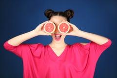 Красивая молодая женщина с грейпфрутом уменьшать около глаз Стоковая Фотография