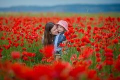 Красивая молодая женщина с девушкой ребенка в поле мака счастливая семья имея потеху в природе на открытом воздухе портрет в мака стоковые изображения rf