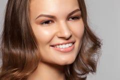 Красивая молодая женщина с длинными коричневыми волосами и белизна усмехаются Стоковое Фото