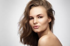 Красивая молодая женщина с длинными коричневыми волосами на серой предпосылке Стоковые Изображения RF