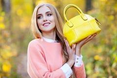 Красивая молодая женщина с желтой модной сумкой в руках на природе осени стоковые изображения