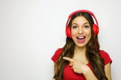 Красивая молодая женщина с красными наушниками слушая к музыке усмехаясь и указывая космос экземпляра на белой предпосылке в крас Стоковое Изображение RF