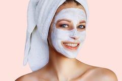 Красивая молодая женщина с лицевой маской на ее стороне Забота и обработка кожи, спа, естественная красота и концепция косметолог стоковая фотография