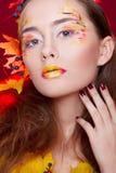 Красивая молодая женщина с осенью составляет держать яблока в ей Стоковое фото RF