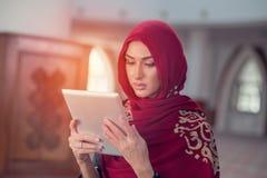 Красивая молодая женщина с планшетом внутри мечети стоковое фото