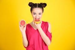 Красивая молодая женщина с половинами грейпфрута Стоковые Изображения