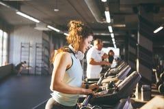 Красивая молодая женщина с сочным вьющиеся волосы в жилете и гетры бежит в спортзале на третбане, cardio машине тренировки и весе стоковое фото