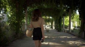 Красивая молодая женщина с темными волосами, нося черными шортами и бежевой футболкой идет в парк с корзиной акции видеоматериалы