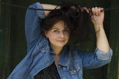 Красивая молодая женщина с темн-коричневыми волосами усмехается на винтажной деревянной предпосылке Портрет усмехаясь европейской Стоковое Фото