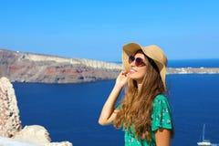 Красивая молодая женщина с шляпой и солнечными очками наслаждаясь солнцем в Santorini с кальдерой на предпосылке, Греции, Европе стоковые фотографии rf