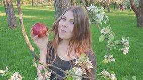 Красивая молодая женщина с яблоком в ее руках против фона яблоневого сада Женщина ест яблоко Сад акции видеоматериалы