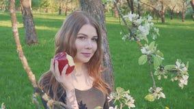 Красивая молодая женщина с яблоком в ее руках против фона яблоневого сада Женщина ест яблоко Сад видеоматериал