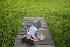 Красивая молодая женщина Таиланда местная лежа на деревянном мосте и слушая радио в поле риса Стоковые Изображения