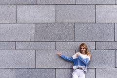 Красивая молодая женщина указывает прочь, смотрящ камеру и усмехаться, стоя против серой стены стоковая фотография