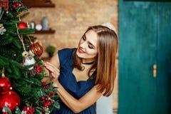 Красивая молодая женщина украшает рождественскую елку Место для ins Стоковые Изображения RF