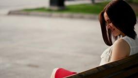 Красивая молодая женщина усмехается загадочно, сидящ на стенде в парке лета Портрет женщины outdoors сток-видео