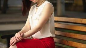 Красивая молодая женщина усмехается загадочно, сидящ на стенде в парке лета Портрет женщины outdoors акции видеоматериалы