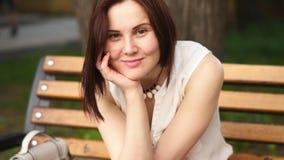 Красивая молодая женщина усмехается загадочно, сидящ на стенде в парке лета Портрет женщины outdoors видеоматериал