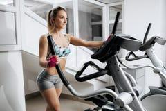Красивая молодая женщина фитнеса на спортзале работая на машинах xtrainer Делать привлекательной пригонки модельный cardio тучно стоковое фото rf