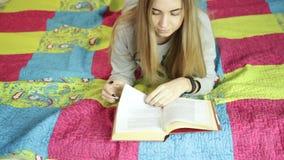 Красивая молодая женщина читая книгу на кровати дома домашний учить видеоматериал
