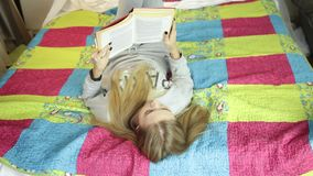 Красивая молодая женщина читая книгу на кровати дома домашний учить сток-видео