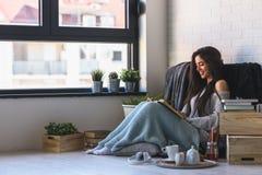Красивая молодая женщина читая кофе книги выпивая наслаждаясь окном Стоковые Изображения