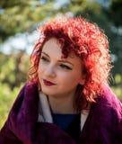 Красивая молодая женщина redhead представляя outdoors Стоковые Фото